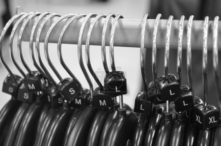 Photo for Monochrome of plastic hangers on rail with sizes - Royalty Free Image
