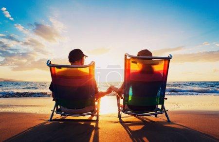 Foto de Senior pareja de hombre y mujer sentada en la playa viendo la puesta de sol - Imagen libre de derechos