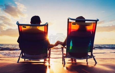 Photo pour Couple âgé de vieil homme et femme assis sur la plage regardant coucher de soleil - image libre de droit