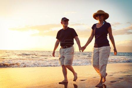 Photo for Senior Couple Enjoying Sunset at the Beach - Royalty Free Image