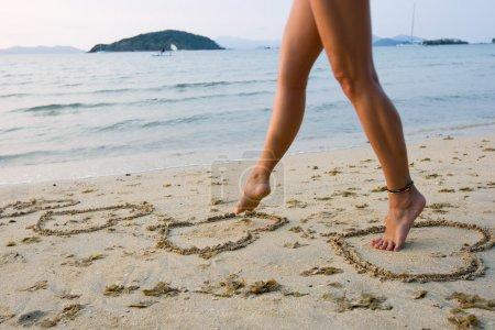 Photo pour Belles jambes de femmes sur le sable de plage - image libre de droit
