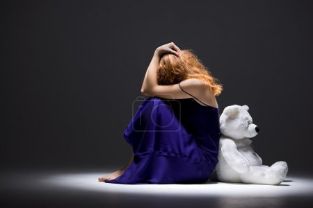 Photo for Loneliness girl is sitting on the floor with toy - Royalty Free Image