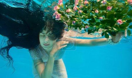 Photo pour Fille dans l'eau avec des fleurs - image libre de droit