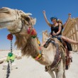 Two girls are ride on camel in desert...