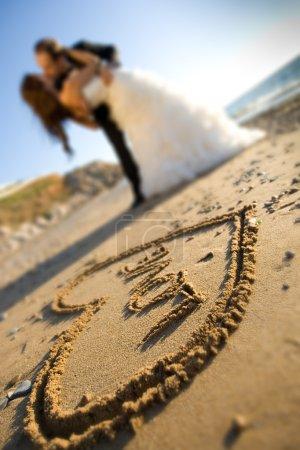 Photo pour Heureux couple de mariage s'embrasse sur la mer - image libre de droit