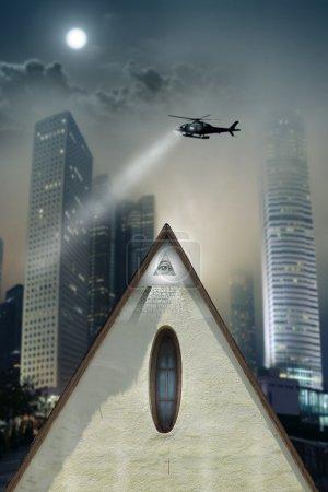 Photo pour Concept photo d'une pyramide en forme de butte avec oeil de providence au milieu d'une ville urbaine gothique avec hélicoptère à la recherche au-dessus - image libre de droit