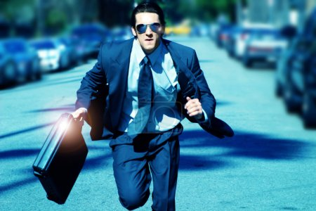Photo for Young business man running with briefcase - Royalty Free Image