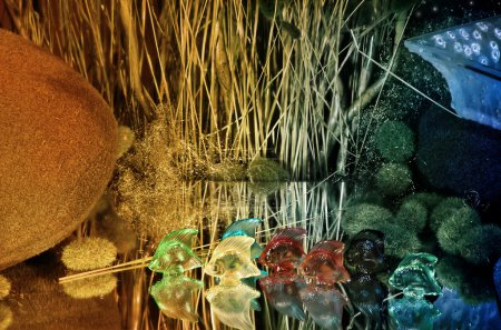 Photo for Colorful glass fishes standing on a mirror with decorations in the background - Royalty Free Image