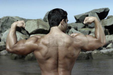 Body builder by the rocks