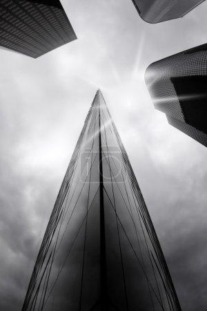 Foto de Rascacielos creando un vórtice convergiendo en el sol detrás de las nubes en blanco y negro - Imagen libre de derechos