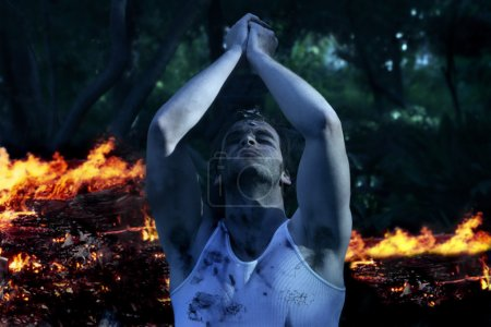Photo for Dramatic portrait of man holding hands to sky against flames - Royalty Free Image
