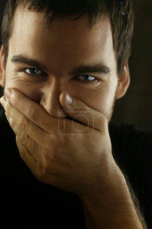 Photo pour Portrait d'homme couvrant le visage avec la main sur le point de rire - image libre de droit