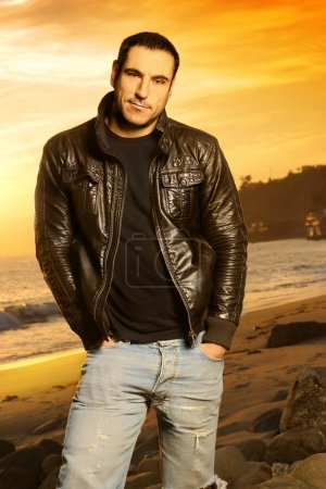 Photo for Full body portrait of good looking man in golden light wearing a leather jacket against beautiful sunset - Royalty Free Image