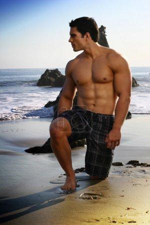 Photo pour Sexy young fit homme sur la plage regardant vers l'océan - image libre de droit