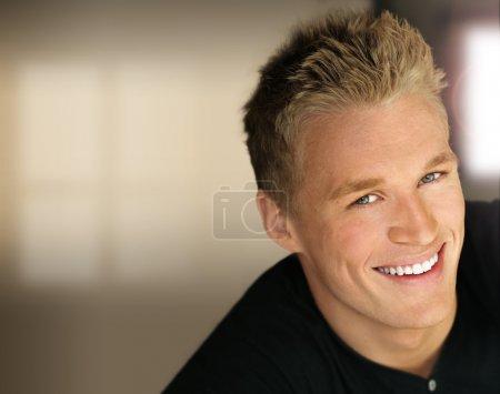 Foto de Retrato de primer plano de un joven y guapo hombre de negocios feliz con luces de estudio y fondo moderno - Imagen libre de derechos