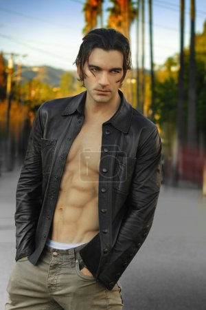 Photo for Fashion portrait of an edgy male model wearing leather jacket and shirtless outdoors - Royalty Free Image