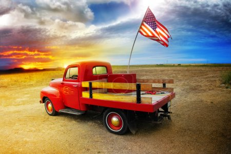 Photo for Red vintage pick up truck with American flag in wide open country side with dramatic sunset cloudscape - Royalty Free Image