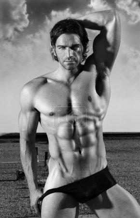 Photo pour Beaux-arts noir et blanc portrait d'un beau modèle masculin musclé en slip noir en pose provocante à l'extérieur - image libre de droit