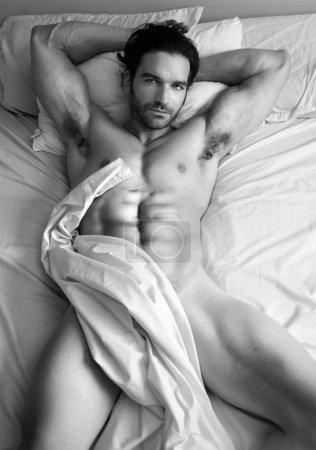 Photo pour Beaux-arts noir et blanc portrait du corps d'un modèle masculin nu au lit - image libre de droit