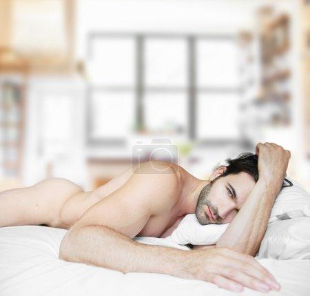 Photo pour Sexy nu mâle modèle dans lit à la maison seul - image libre de droit
