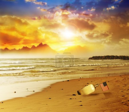 Flag in bottle on beach with sunset