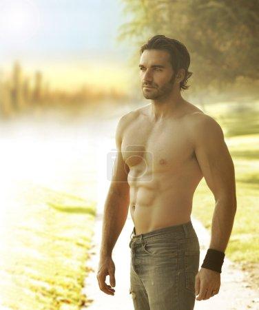 Photo pour Portrait d'un bel homme torse nu en jeans contre la lumière dans un cadre extérieur naturel - image libre de droit