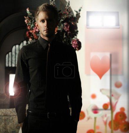 Photo pour Concept portrait avec éclairage dramatique d'un jeune homme en tenue formelle et fond de coeur - image libre de droit