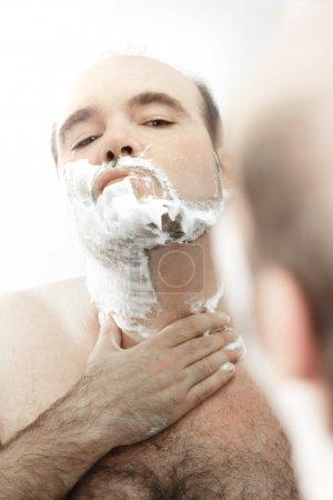Photo pour Portrait d'un homme chauve se rasant dans un miroir - image libre de droit