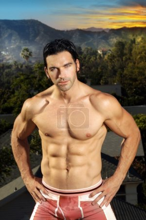 Photo for Very fit male muscular model with exotic background and sunset - Royalty Free Image