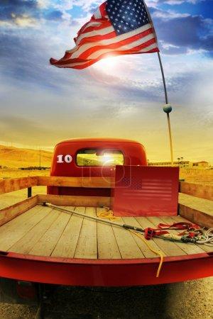 Photo pour Photo de la notion d'un millésime vintage rouge ramasser camion avec drapeau américain dessus contre rural cloudscape dramatique - image libre de droit