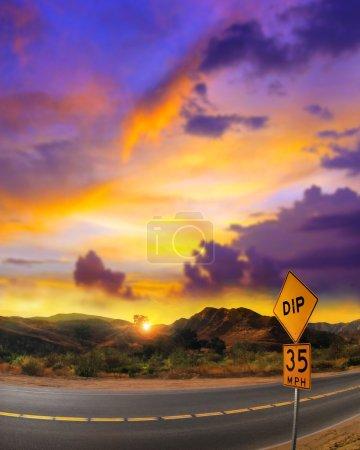 Photo pour Désert en lumière rose avec panneau de signalisation et montagnes rocheuses en arrière-plan - image libre de droit