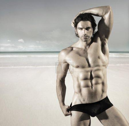 Photo pour Portrait sexy d'un mannequin de fitness masculin sexy buff tirant sur ses slips de bikini sur la plage - image libre de droit