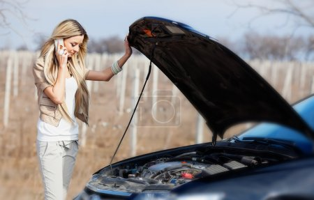 Photo for Beautiful blond girl calling cellphone near her broken car - Royalty Free Image