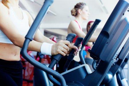 Photo pour Femme les mains sur la machine dans un centre de fitness de suivi - image libre de droit