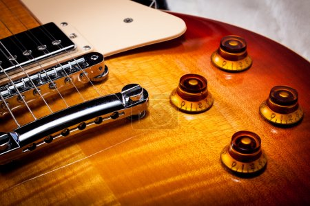 Photo for Close up macro shot of the body of a sunburst electric guitar with gold volume knobs - Royalty Free Image