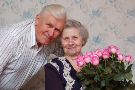 Happy old couple and big bouqet of pink roses...