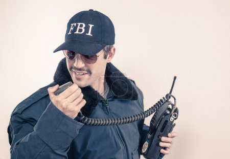 Investigative cocky FBI agent wearing blue jacket, sunglasses, and mustache