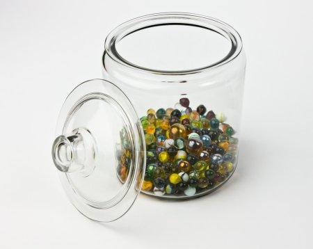 bocal en verre moitié plein de billes de verre coloré