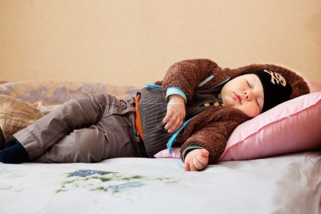 Cute little boy sleeps in the clothes on a bed