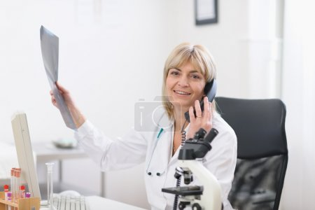 Middle age doctor woman holding patients roentgen and speaking phone