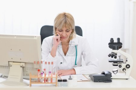 Concentrated middle age doctor woman working at office