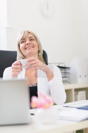 Middle age business woman having cup of coffee and dreaming