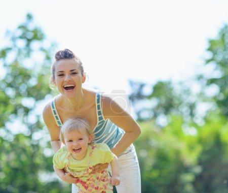 Photo pour Heureuse mère et bébé jouer dehors - image libre de droit