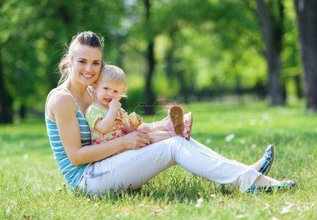 Photo pour Heureuse mère et bébé assis sur l'herbe dans le parc - image libre de droit