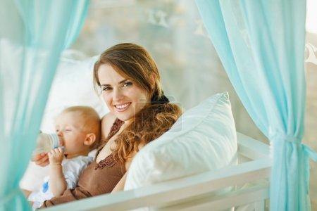 Photo pour Femme heureuse nourrissant bébé - image libre de droit