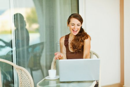 Excited young woman working on laptop on terrace with cup of coffee