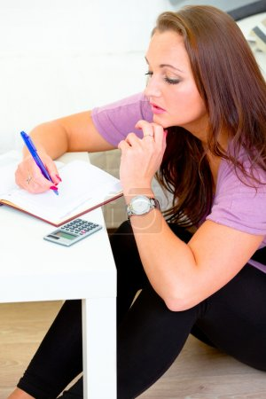 Pensive lovely woman sitting on floor and making notes in diary