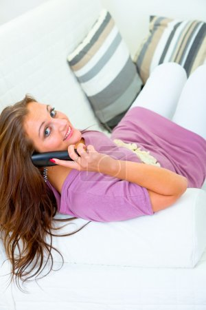 Photo for Smiling pretty woman sitting on sofa at home and talking on phone - Royalty Free Image