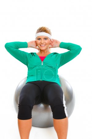 Fitness girl making abdominal crunch on fitness ball isolated on