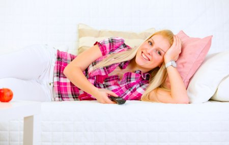 Photo for Smiling pretty woman lying on sofa and watching TV - Royalty Free Image
